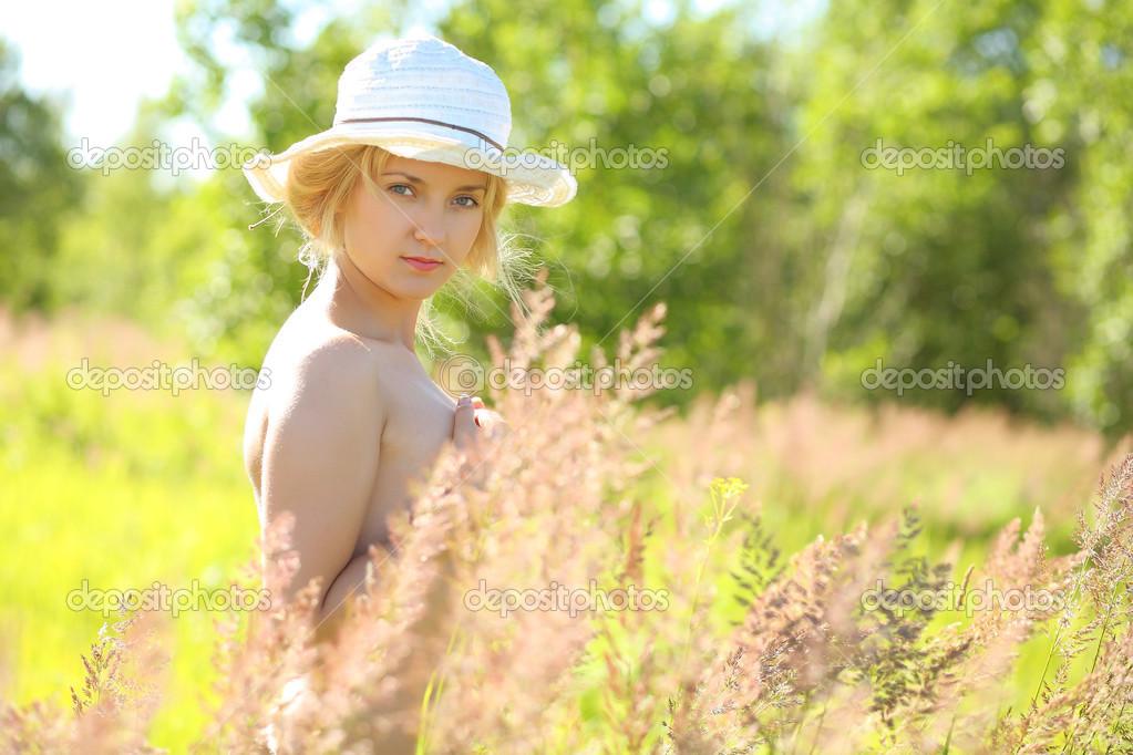 Schöne und schöne junge Mädchen, die nackt im Gras steht