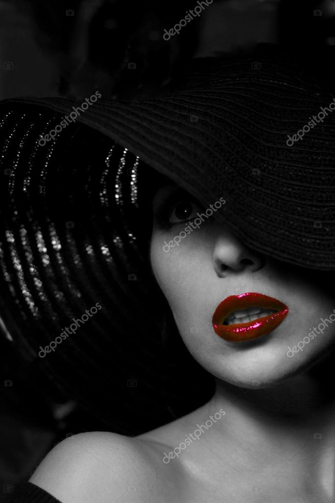 Mysterious woman in black hat red lips stock photo