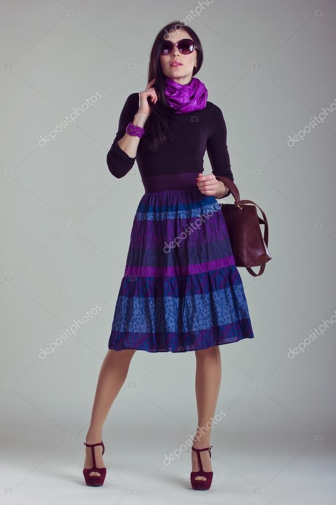 fdfcf93cb4 Divat magazin lőni. gyönyörű fiatal nő fekete jumper, kék-lila szoknya,  sál, bordó táska és cipő fehér háttér. finom stílusban. új megjelenés —  Fotó ...