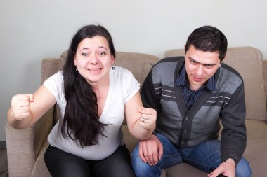 Young couple watching sport TV at home