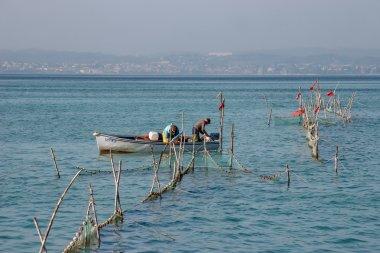 Fishermen checking their nets at Lake Garda