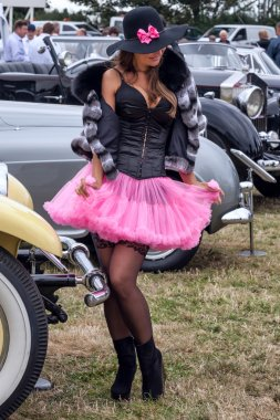 Lady posing beside cars at Goodwood Revival