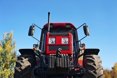 Modern red tractor on a blue sky background.