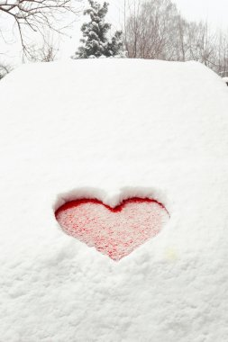 Love red heart shape in snow on red car. Close-up.
