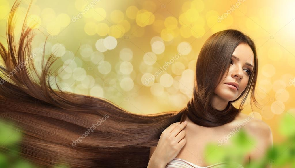 Portrait of beautiful young woman with brown long hair over green background