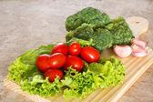 brokolice, rajčata, salát a česnek na dřevěné desce