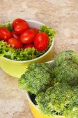 Fresh broccoli, cherry tomatoes, salad in bowls