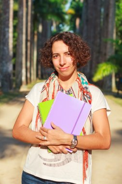 Young happy smiling woman (student, teacher) holding books and notebooks