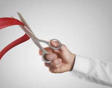 Hand cutting red ribbon with scissors