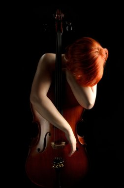 Girl leaning against cello on black background