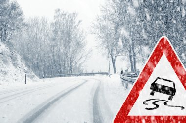 Winter driving - snowfall on a country road with warning sign