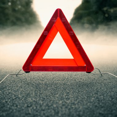 Caution fog - warning triangle on a foggy road