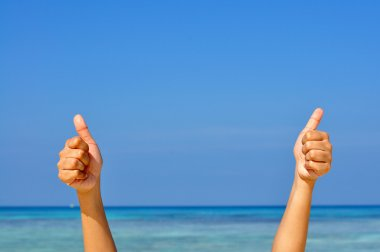 Two hands with thumb up on blue sky and sea background