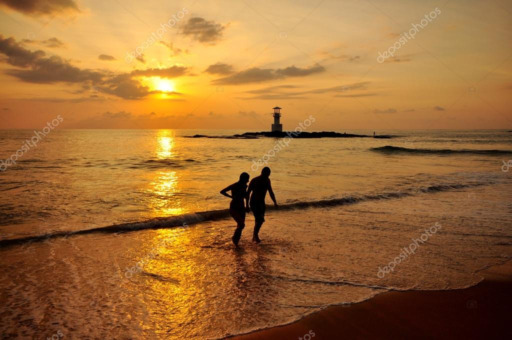Silhouette romantic scene of couples on the beach with sunset ba