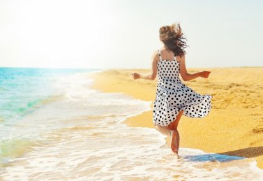 Young happy woman running on the beach back to camera