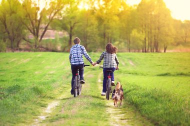 Young happy couple ride bicycles