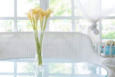 Yellow flower in vase on table and window sill background. Vinta