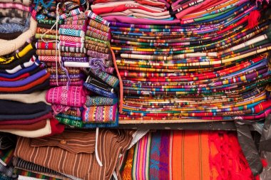 Bright coloured fabrics in Ecuadorian Market. Pinks,reds, blues, every color of the rainbow in fact displaying ponchos, rugs and scarves