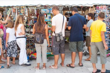 Tourists in front of the newsstands with papers and postcards