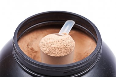 Scoop of chocolate whey isolate protein in a black plastic conta