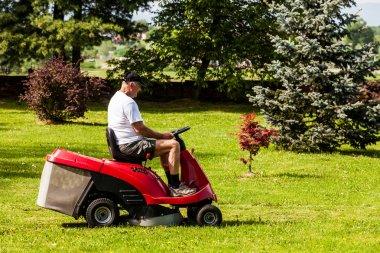 Senior man driving a red lawn mower