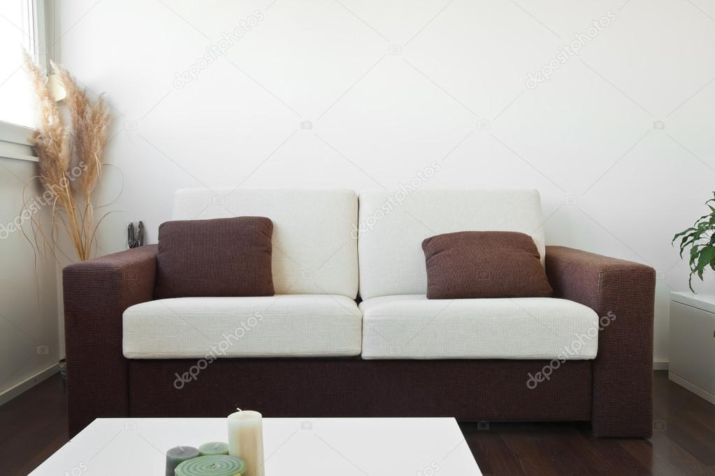 weißer und brauner Stoff Sofa im Wohnzimmer mit braunen cushio ...