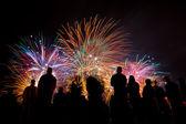 Fotografie velké ohňostroje s siluety lidí, sledovat to