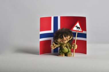 A small norwegian troll hitchhiking and holding a road sign with an elk and Norway flag at the background