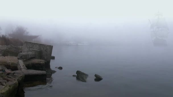 Sailboat in full sail comes up out of fog