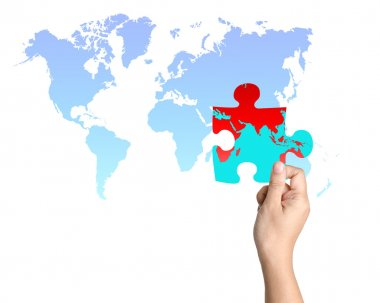 One jigsaw piece of world map held in a hand