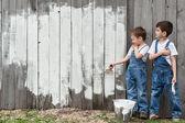 Chlapci s kartáčky a malování na starou zeď