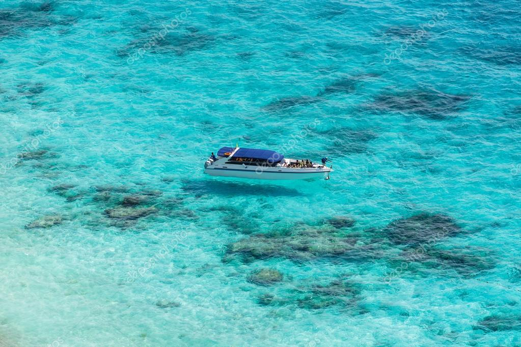 Aerial view of the tropical island, clear blue sea and a boat at