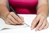 Frau Hände halten einen Stift, einen Text zu schreiben