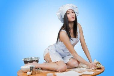 sexy girl wearing chef prepares dough.