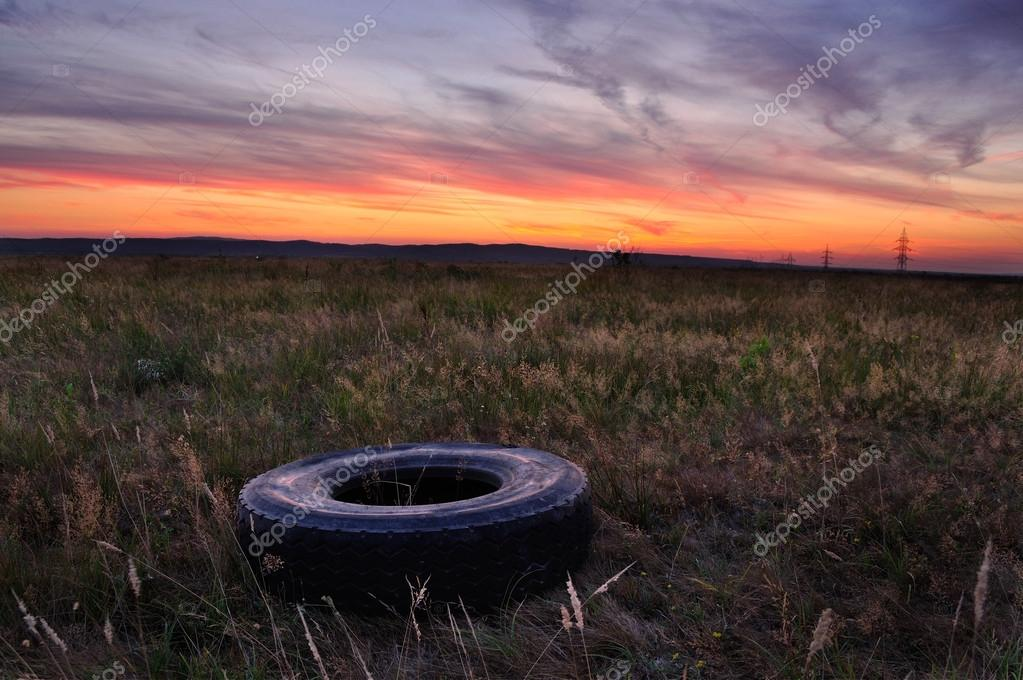 Late autumn sunset with tyre on the ground. Flat tire concept.
