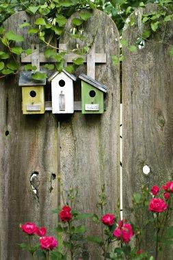 Flower garden birdhouses on a rustic fence