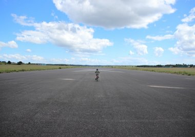 Biking child with helmet on airplane runway