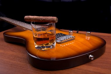 Glass of rum and cigars on the electric guitar