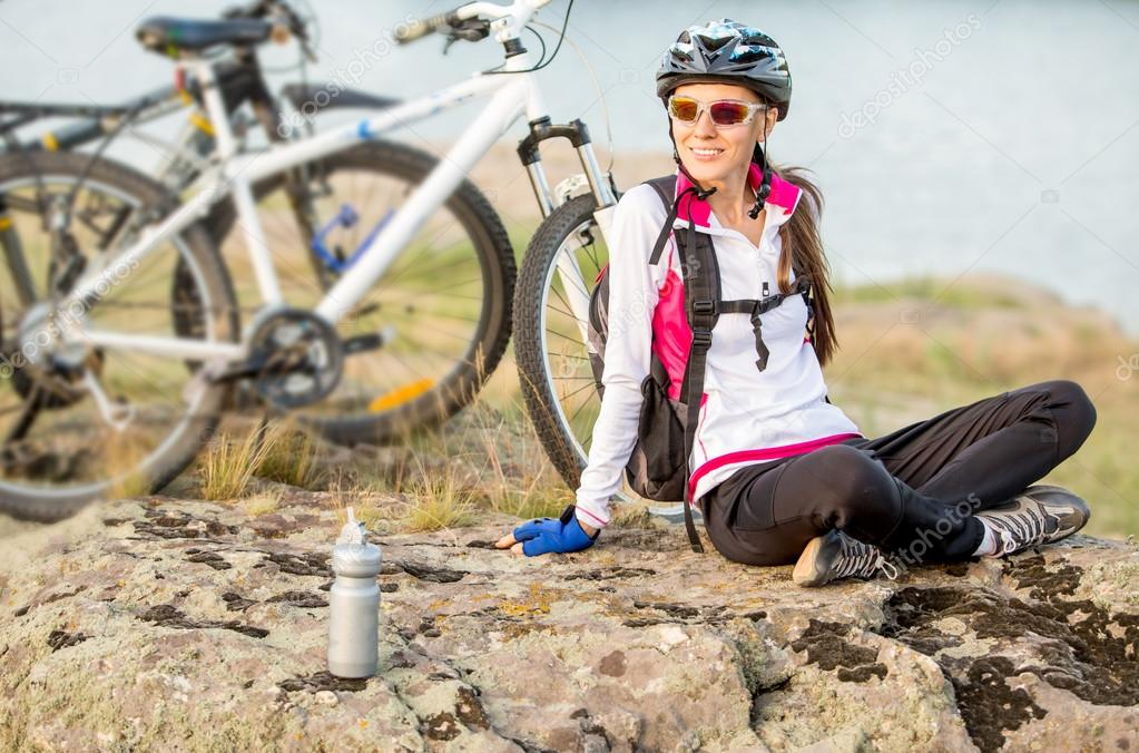 Sport bike woman sitting on a mountain next to bike relaxing and enjoying nature