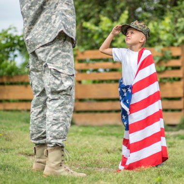 American soldier and his son salute each other