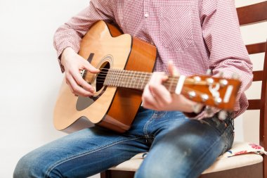 Photo of man sitting on chair and playing on acoustic guitar