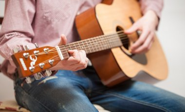 Man in jeans sitting and playing guitar