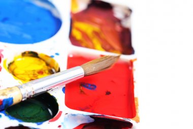 artists palette with various colour paints and brush