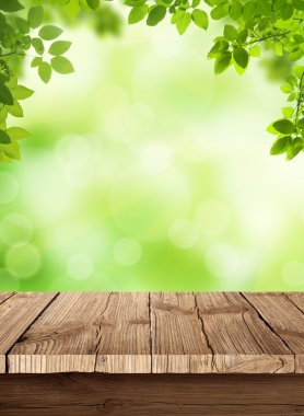 Fresh spring green bokeh background with wooden table for your products displays