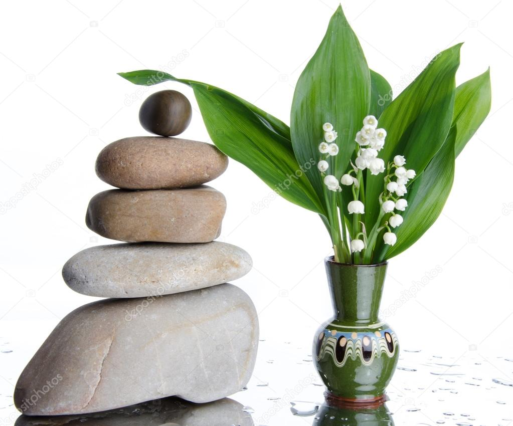 Composition of stacked pebbles with a vase of lilies