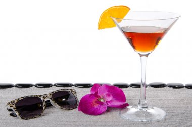 Cocktail glass with sunglasses, a flower and  black pebbles on t