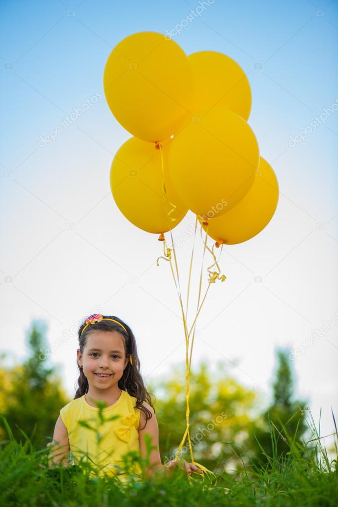 Happy girl with yellow balloons