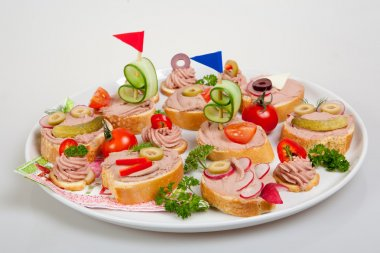 party platter with sandwiches with pate and vegetables