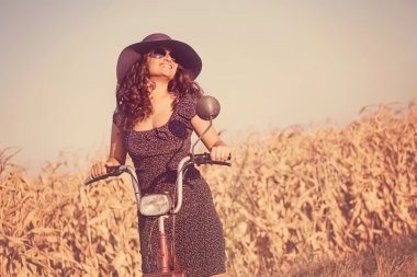 young smiling woman with hat and sunglasses, on scooter