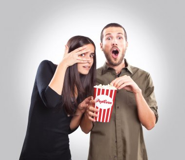 Young couple watching a movie and eating popcorn